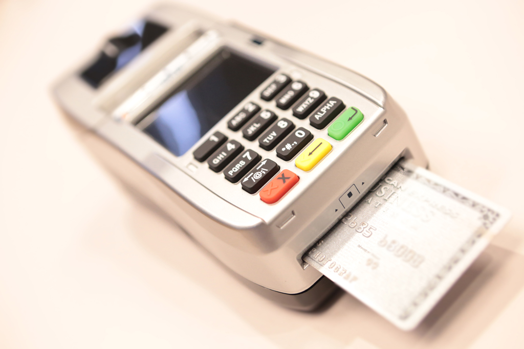 silver American express chip card shown dipped, or being processed, in an emv terminal
