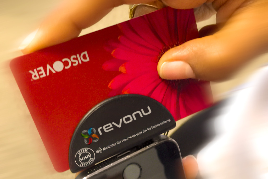 Red Discover card swiped through mobile payment processor attached to iPhone