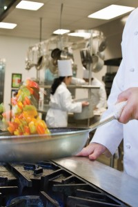 Male chef in kitchen of a COCARD restaurant merchant account holder with pan of vegetables over stove